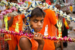 Indian boy with religious equipment, Benares. Young boy wearing orange cloths on a pilgrimage to holy river Ganges in Varanasi holding atributes of God Shiva on Royalty Free Stock Photo