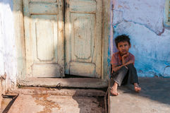 An Indian boy sits in front of a doorway Stock Photography