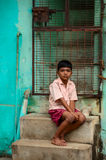 Indian boy sitting near colorful wall of his house Stock Photography
