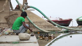 Indian boy sorting dishes for cleaning at shore of Ganges in Varanasi. stock footage