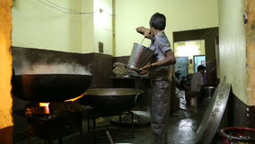 Indian boy working with large kettles on fire in workshop in Jodhpur. stock video