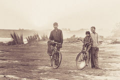 Indian boys on the bicycles. Indian boys posing for a photo on the riverbank in Agra, India Stock Photo
