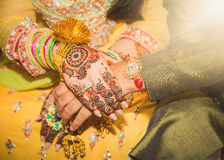Indian bride and groom holding hands. One day before marriage, showing their decorated hands with Henna and tattoo. Bride Wearing gold bangles and rings Royalty Free Stock Photos