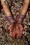 Indian Bride with Henna. Indian bride wearing a heavily ornamented sari with intricate henna designs on her arms and hands royalty free stock images