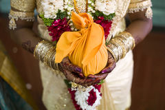 Indian bride with henna design. Indian bride with henna decoration on her hands, holding one of the wedding presents Stock Photography