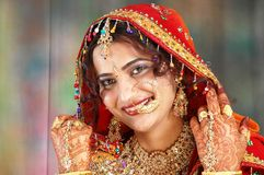 Indian bride in her wedding dress showing. Beautiful Indian bride on her wedding day in her traditional dress and showing her hand colored with henna and full of Stock Photos