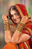 Indian bride in her wedding dress showing bangles. Beautiful Indian bride on her wedding day in her traditional dress and showing her hand colored with henna and Stock Images