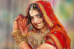 Indian bride in her wedding dress showing henna. Beautiful Indian bride on her wedding day in her traditional dress and showing her hand colored with henna Royalty Free Stock Image