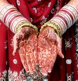Indian bride showing Mehndi design. And gold bracelet and colorful bangle stock photography