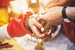 Indian bride ties with holy thread on her wrist at ceremony focus on hand with blurry background. Men ties the holy thread on the wrist of indian bride during Stock Photography