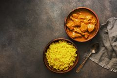 Indian and British dish spicy chicken tikka masala with rice on a dark rustic background. Top view, flat lay