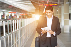 Indian business male using tablet computer. While waiting for train Royalty Free Stock Image