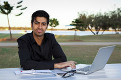 Indian business man. Young indian businessman working on laptop at park table Stock Image