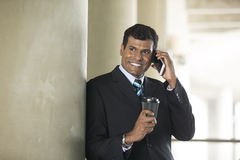 Indian business Man using his Smart phone. Royalty Free Stock Images