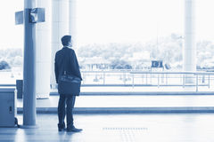 Indian business man waiting bus. Rear view full body Asian Indian business man waiting bus at public bus station, in blue tone Royalty Free Stock Image