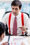 Supervisor talks to subordinate professional in office building Stock Photos