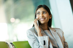 Indian business woman. Cheerful indian business woman talking on mobile phone at airport Royalty Free Stock Images