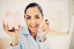 Indian business woman saving money piggy bank. Indian business woman saving money in piggy bank Stock Images