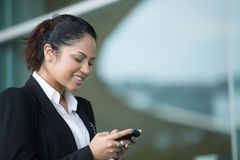 Indian business woman texting on mobile phone. Royalty Free Stock Photos