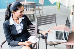 Indian Business woman working with laptop. Sitting on terrace in front of city skyline Royalty Free Stock Photo