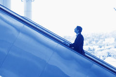 Indian businessman ascending escalator Royalty Free Stock Photography