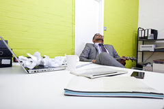 Indian businessman asleep at his desk clutching ukulele Stock Photography