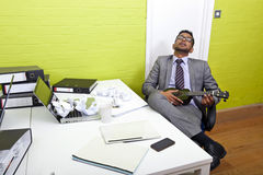 Indian businessman asleep at his desk clutching ukulele Royalty Free Stock Images