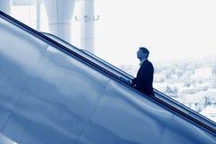 Indian businessman going up escalator stock photos