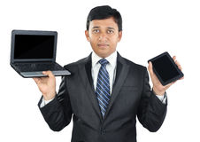 Indian Businessman Holding Laptop and Tablet Stock Photo