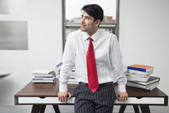 Indian businessman leaning on desk while looking away in office Stock Photo