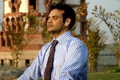 Indian Businessman meditating. Young Indian business man meditating near a temple Stock Image