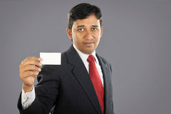 Indian businessman showing business card. Portrait of Indian businessman showing business card Royalty Free Stock Photo