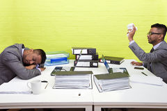 Indian businessman throwing paper at his sleeping twin Royalty Free Stock Image