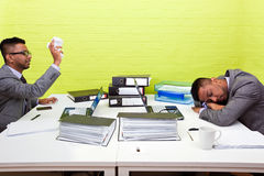 Indian businessman throwing paper at his sleeping twin Stock Photo