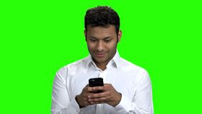 Indian businessman typing message on mobile phone. Handsome man in white shirt using cell phone on Chroma Key background stock video footage