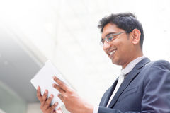 Indian businessman using digital tablet pc. Candid young Asian Indian businessman using digital tablet pc at outdoor building. India male business man, real Stock Photos