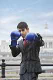 Indian businessman wearing blue boxing gloves with St. Paul's Cathedral in the background Stock Image