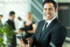 Indian businessman working. Cheerful young indian businessman working on tablet computer in office Stock Image