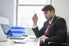 An Indian businessman working at office desk Stock Image