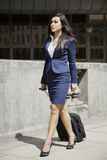 Indian businesswoman in formal clothing walking with wheeled bag Royalty Free Stock Images
