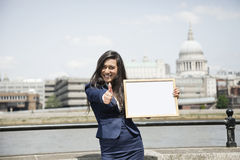 Indian businesswoman gesturing thumbs up as she holds a sign with St. Paul's Cathedral in background Stock Images