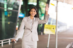 Indian businesswoman hailing taxi. Happy indian businesswoman hailing for a taxi after arriving at airport Stock Image