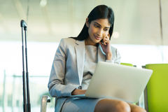 Indian businesswoman laptop airport. Successful indian businesswoman using laptop computer at airport Stock Image