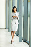 Indian businesswoman smart phone. Happy indian businesswoman using smart phone in modern office Stock Photography