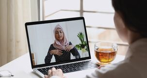 Indian businesswoman wears hijab communicates with distance worker by webcam