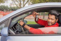 Indian car buyer with keys. Indian man sitting in the car showing car keys. concept of car rental, automobile business or vehicle ownership royalty free stock images