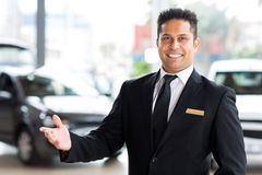 Indian car dealer. Happy young indian car dealer standing inside showroom Stock Images