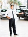 Indian car salesman. Good looking indian car salesman standing at showroom presenting new cars stock image