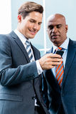 Indian and Caucasian business man using phone Stock Photography