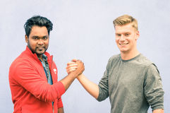 Indian and caucasian men shaking hands in a modern handshake. To show each other friendship and respect - Best friends having arm wrestling against racism on Stock Photos
